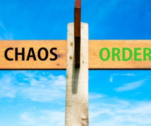 Wooden signpost with two opposite arrows over clear blue sky, Chaos versus Order messages